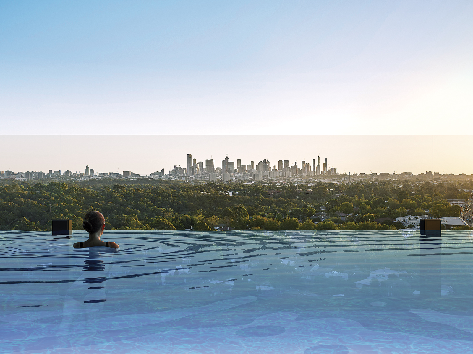 Woman gazing from rooftop pool at HOME by Caydon towards Melbourne CBD