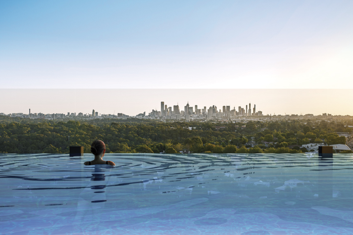 Woman in sky pool at HOME By Caydon with views of Melbourne CBD - Render - Binyan Studio