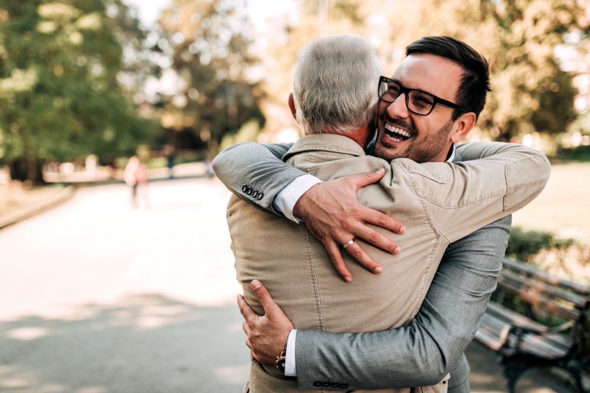 HOME By Caydon Stock Young man embraces older man in park 1200x800
