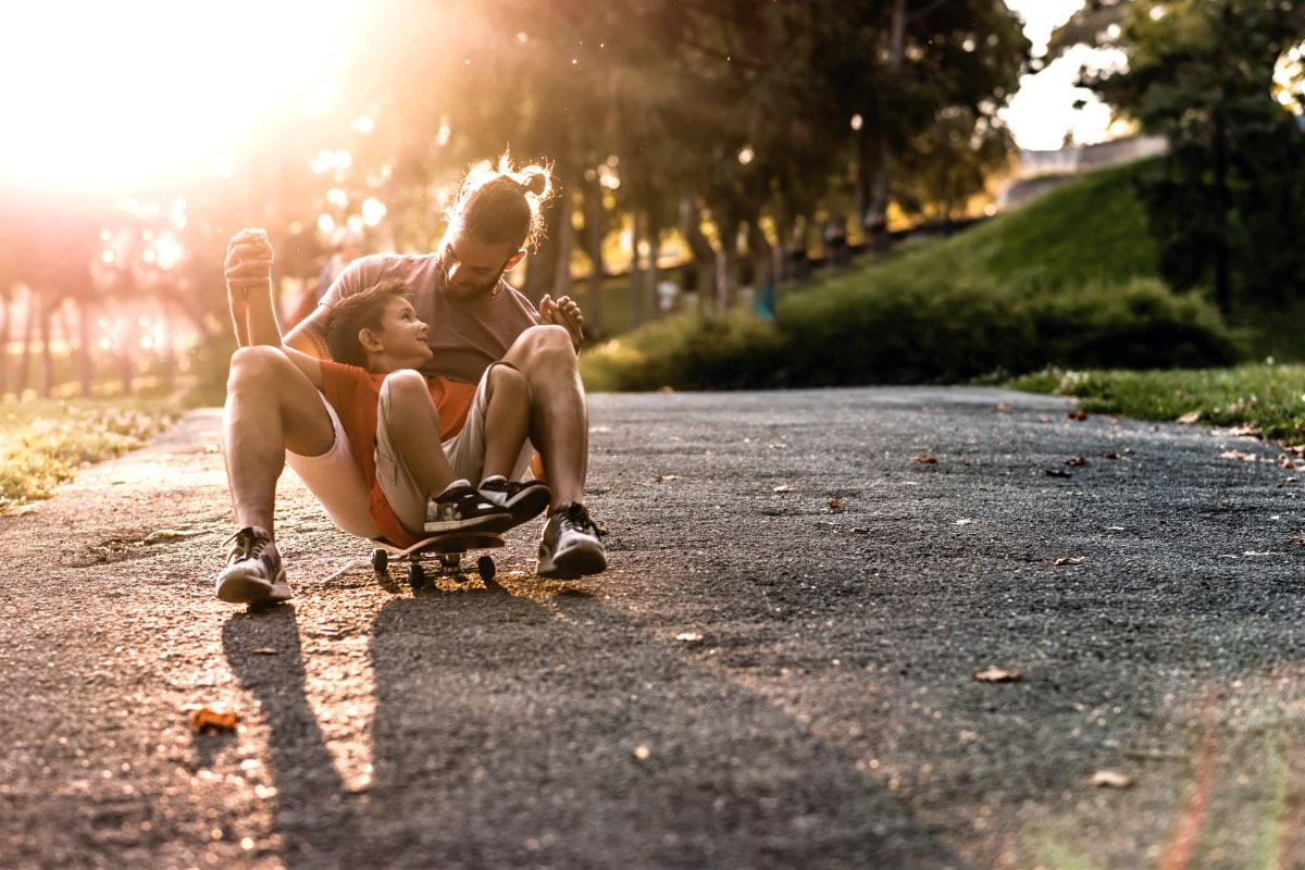 HOME By Caydon Stock Photography Dad with young boy on skateboard in park